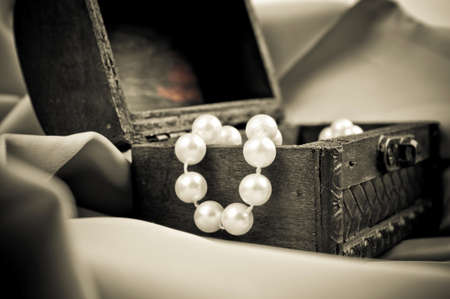 Close-up shot of the pearls in the open wooden chest, on the beige satin