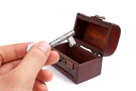 Hand holding key with decorative (treasure chest) box, isolated on white photo