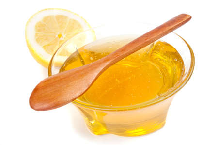 Wooden spoon on the bowl with honey and half lemon, isolated on white photo