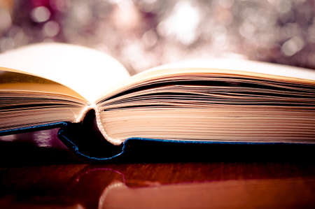 Open book on the wooden table and bokeh effect in the background photo