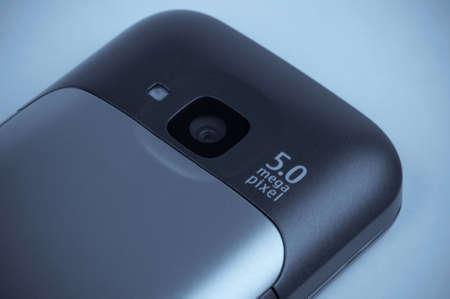 Macro shot of five mega pixel camera on the mobile phone - blue toned image photo
