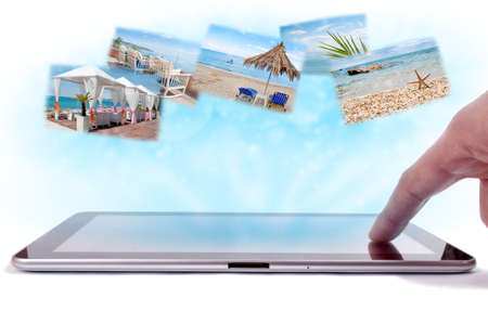 Finger on the tablet touch-screen and sea holiday images in the blue rays from tablet screen photo