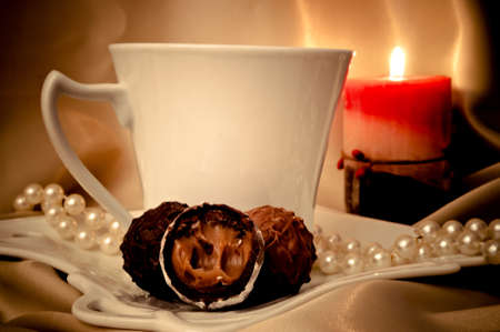 Stuffed chocolate sweets, coffee, pearls and candle on the beige satin