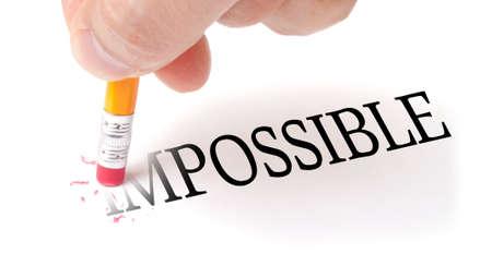 actitud positiva: La mano masculina que sostiene un l�piz de madera y las letras de borrado I & M de la palabra IMPOSIBLE