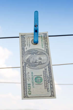 Hundred-dollar bill dry on the wire with sky in the background photo