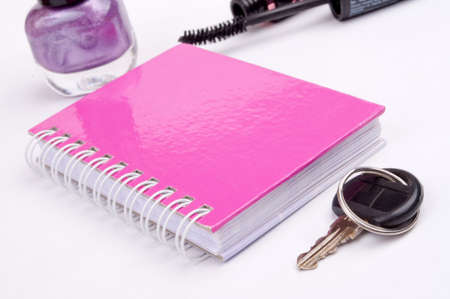 Pink notebook, key, nail polish and mascara in the background, isolated on white photo
