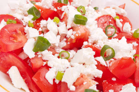 Fresh tomato salad with goat feta cheese and young chopped onion sprout photo