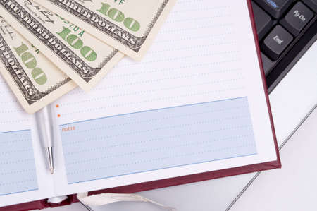 Planner and hundred-dollar bills on the laptop photo