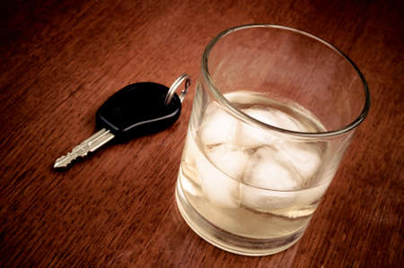 Glass with alcoholic beverage and car key on the wooden table photo