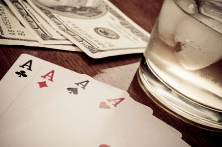 Poker of aces on the wooden table, whiskey with ice cubes and hundred-dollar bills in the background photo