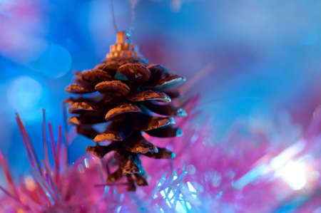 Christmas decorative pinecone hanging on the branch with blue lights from a lightbulbs in the background photo
