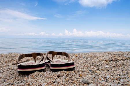 Male thongs on the sand beach with sea and sky in the background photo