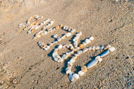 The word dreams made ??of small stones on the sandy beach photo