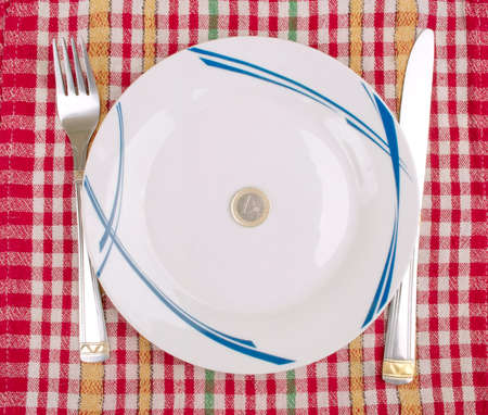 One Euro coin on the plate and fork and knife on the table - crisis concept Stock Photo - 13997951
