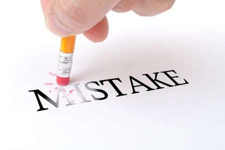 """mistakes: La mano masculina que sostiene un l�piz de madera y eliminar la palabra """"error"""" en el papel blanco"""