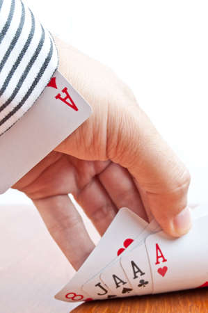 Male hand holding trilling of aces and one ace in the sleeve photo