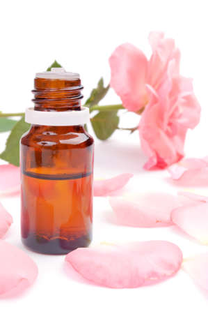Essential oil in the bottle, pink rose petals around and rose in the background photo