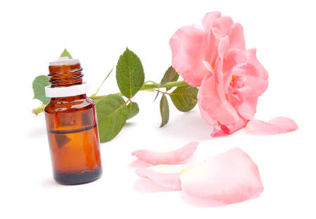 Essential oil in the bottle, pink rose petals around and rose in the background