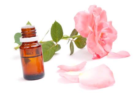 olio corpo: L'olio essenziale nella bottiglia, rosa, petali di rosa intorno e rosa sullo sfondo