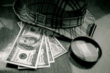 American Dollar-bills, loupe and hat on the wooden table photo