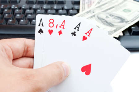 Male hand holding poker of aces and blurred american Dollar-bills on the computer keyboard in the background photo