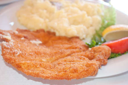 Breaded chicken steak with mashed potatoes served on a plate photo