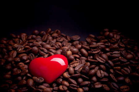Red heart on the coffee beans in the dark with directed light