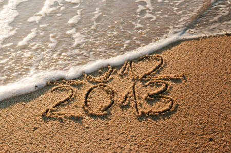 2012 and New year 2013 coming - waves erase year 2012 on the sandy beach