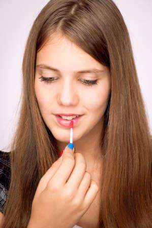 Beautiful teenage girl putting lip gloss on the lips photo