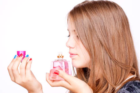 Teenage girl smelling perfume bottle, isolated on white photo