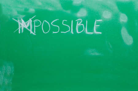 Cross out letters IM, in the word IMPOSSIBLE on the green school board photo
