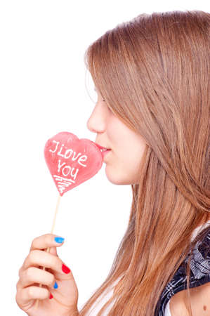 Teenage girl with heart-shape lollipop and words I Love You, isolated on white photo