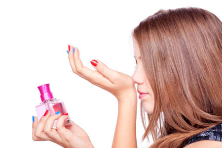 Teenage girl holding perfume and smelling perfumed hand, isolated on white