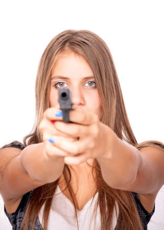 Teenage girl holding a gun, isolated on white - focus on the eyes and blurred gun photo