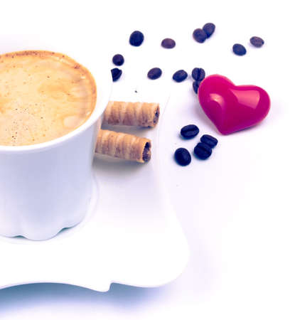 Hot coffee with chocolate rolls, coffee beans and heart on the white background photo