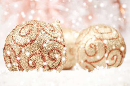 Snow falling over golden Christmas baubles photo