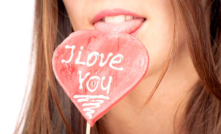 Girl licking heart-shape lollipop with words I Love You photo