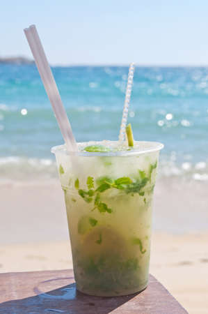 Mojito cocktail on the beach with blurred sea in the background photo