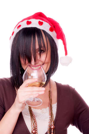 Beautiful brunnete with Santa cap drinking white wine, isolated on white photo