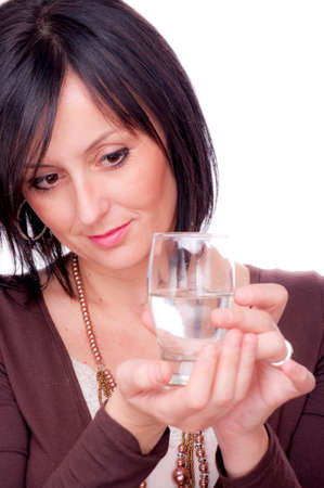 Woman holding a half full glass of water on the white background photo