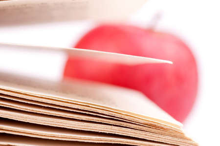 Macro shot of a book pages and blurred apple in the background, isolated on white photo