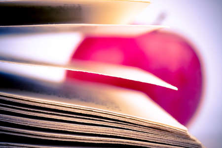 Macro shot of a book pages and blurred apple in the background photo