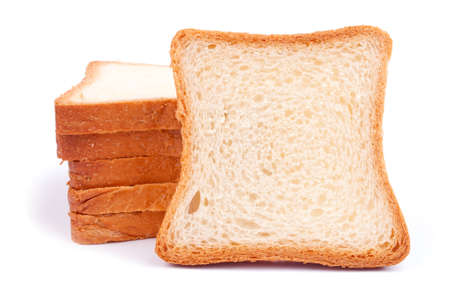 A heap of bread slices and one slice like a copy space, leaning on the heap - isolated on white Stock Photo - 16627885