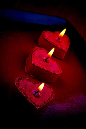 Three heart shape burning candles in the dark photo