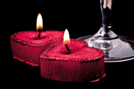 Two burning heart shape candles and wineglass grip on the black background photo