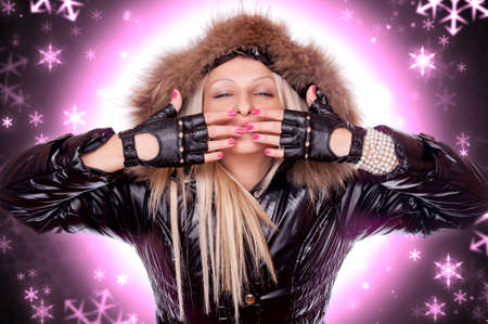 Beautiful blonde in the winter jacket sending kisses with snowflakes in the background Stock Photo - 16763468