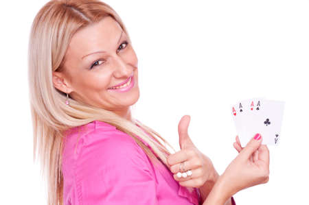 Lovely blonde in a pink jacket holding poker of four aces and showing ok with thumb-up, isolated on white photo