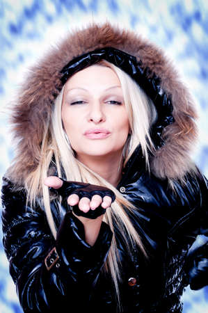 Beautiful blonde in the winter jacket sending kisses with blurred background Stock Photo - 16880515