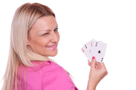 Lovely blonde in a pink jacket holding poker of four aces and winks, isolated on white photo