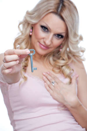 Beautiful blonde holding key in one hand while the other hand hold on a heart, isolated on white - key for my heart Stock Photo - 17079994
